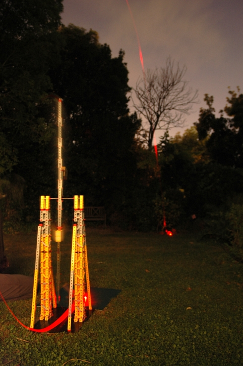 Trebuchet fired at night, with red LEDs and battery attached to the projectile